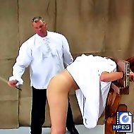 The headmaster and the teacher place Tina in a guillotine then lift up her dress and give her a caning she won`t soon forget